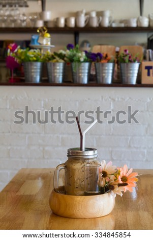 Decorated iced coffee served in a glass with a handle placed in wooden bowls with syrup in coffee shop, with beautiful flowers on a wooden table.