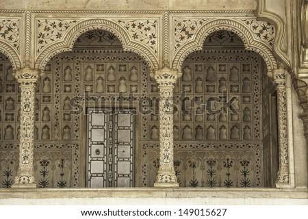 Decorated marble wall frames gate and door at Agra Fort Palace in India.