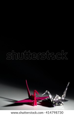Decorated origami cranes isolated on black background - stock photo