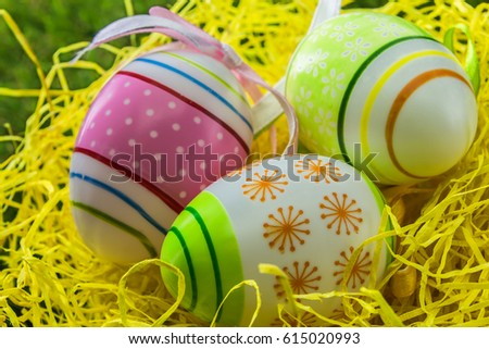 decorated painted Easter eggs on yellow straw and spring grass