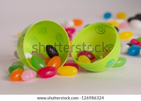 Decorated Plastic Easter Egg Open With Colorful Jelly Beans Out Of Focus In Background Isolated