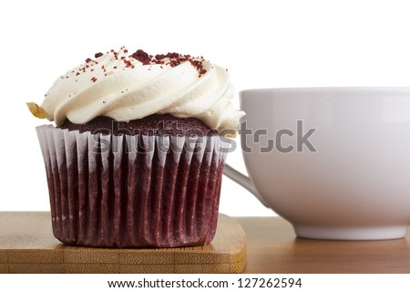 Decorated red velvet cupcake next to a white cup. - stock photo