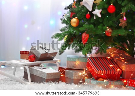 Decorated room with Christmas tree and presents under it, close up
