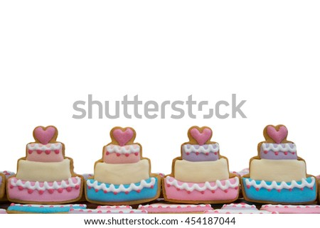 Decorated royal icing cookies in cake shape arranged as bottom part of picture frame - isolated on white background - stock photo