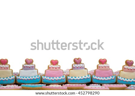 Decorated royal icing cookies in cake shape arranged as lower photo frame - isolated on white background - stock photo