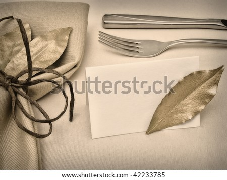 decorated table serving with golden bay leaves in serviette and cord near knife, fork and guest card at beige - stock photo