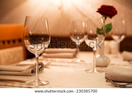 decorated table with glasses of wine and a rose in  vase