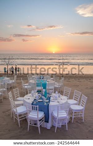 decorated table with plates and serviettes with sunset  - stock photo