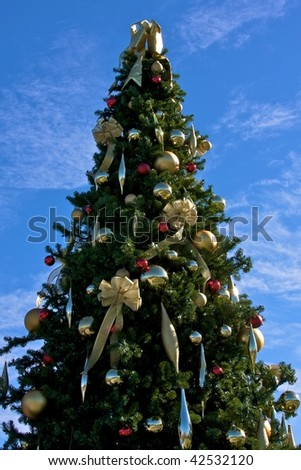 decorated tall christmas tree against blue sky background with wispy white clouds - Tall Christmas Tree