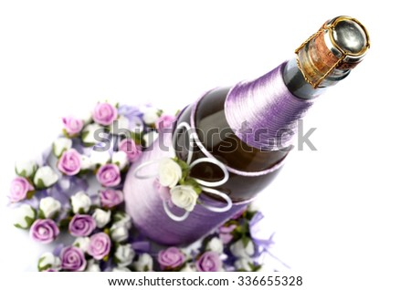Decorated wedding bottle of champagne with roses, isolated on white  - stock photo