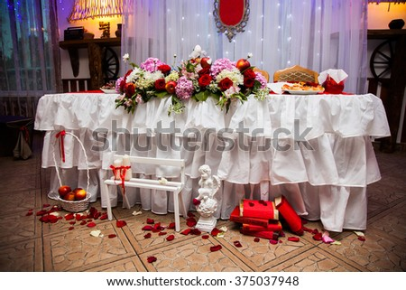 decorated wedding table, wedding souvenirs, wedding flowers, red roses, apples, books, sandwiches, decorative candles, petals, mixed light - stock photo