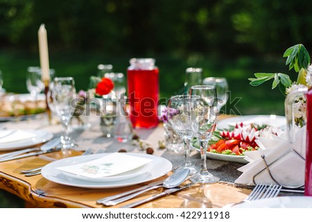 Decorated wedding table with candles in the garden - stock photo
