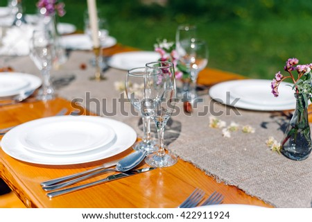 Decorated wedding table with candles in the garden. Beautiful wine glasses on the table - stock photo