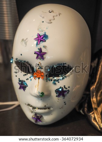 Decorated white plastic face masks on a table - stock photo