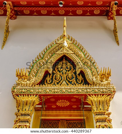 Decorated with the gold plated traditional Thai pattern of arch on the top of windows and eaves on the roof of the Buddhist temple in Thailand