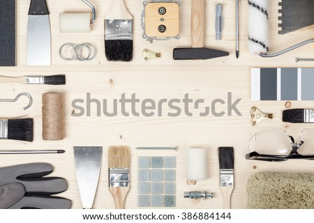 decorating and house renovation tools and accessories on wooden background. flat lay frame composition with copy space top view - stock photo