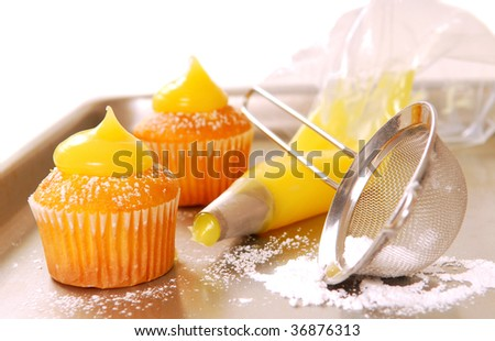 Decorating cupcakes with lemon curd and powdered sugar - stock photo