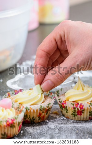 Decorating cupcakes with sweets