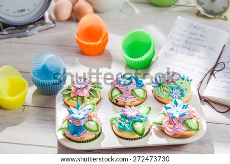 Decorating delicious cupcakes with cream - stock photo