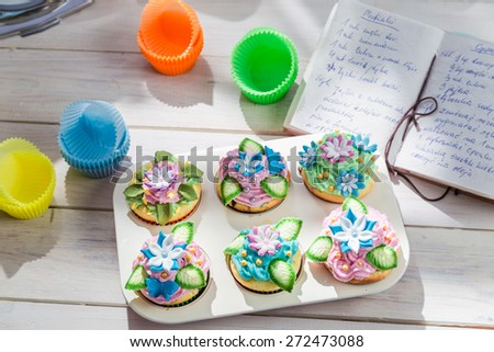 Decorating delicious cupcakes with sweet cream - stock photo