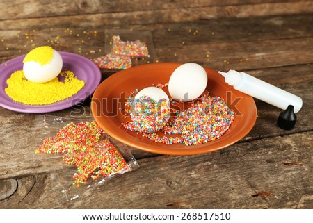 Decorating Easter eggs on color plate on wooden table, closeup - stock photo