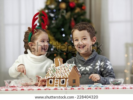 Decorating gingerbread house   - stock photo