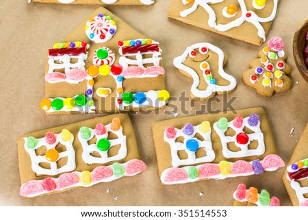 Decorating gingerbread house with royal icing and colorful candies.