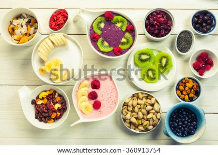 Decorating of Pink strawberry and blue acai berries smoothie bowl with superfood ingredients, Clean eating breakfast concept, top view, white wooden table, rustic style - stock photo