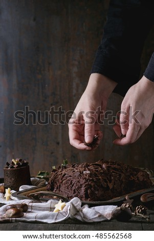 Decorating process of homemade Christmas chocolate yule log by woman's hands with chocolate chips over old wooden table with holly branch and chestnuts. Dark rustic style.