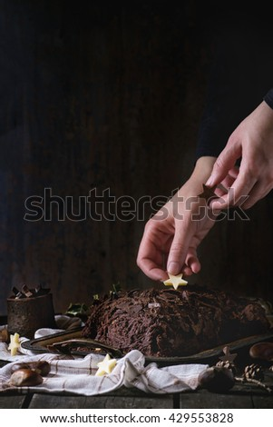 Decorating process of homemade Christmas chocolate yule log by woman's hands with chocolate stars over old wooden table with holly branch and chestnuts. Dark rustic style. - stock photo