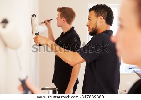 Decorating team painting a room in a house - stock photo