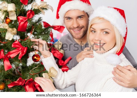 Decorating tree for Christmas. Top view of cheerful young couple decorating a Christmas tree and smiling at camera