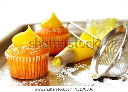 Decorating vanilla cupcakes with lemon curd and powdered sugar - stock photo