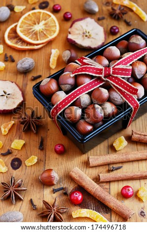 Decoration - hazelnut in baking pan and mixed spices and dried fruits on wooden table - stock photo