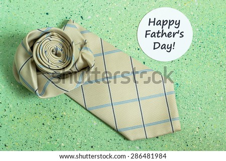 Decoration idea for Father's day -  tie in the shape of a rose and a sticker with the words: Happy Father's Day on a green colored background - stock photo