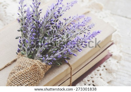 Decoration in French style - bunch of lavender covered with burlap and book bundle placed on vintage crocheted doily - stock photo