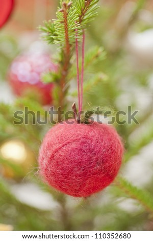 Decoration in shape of an apple hanging in a christmas tree