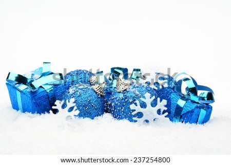 Decoration of blue christmas baubles and gifts on snow white background - stock photo
