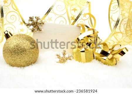 Decoration of golden christmas baubles and gifts with ribbon with wishes card on snow white background - stock photo
