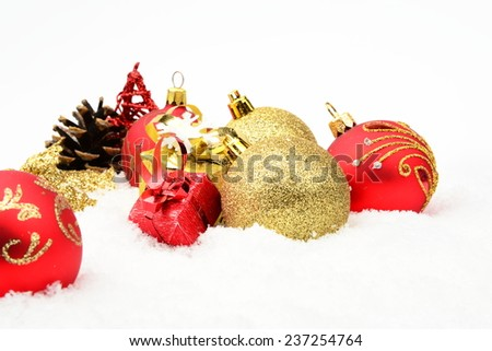 Decoration of golden,red christmas baubles and gifts on snow white background - stock photo