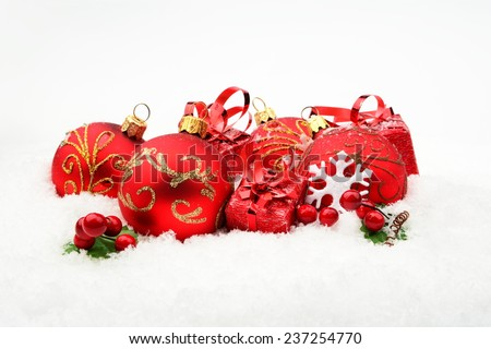 Decoration of red christmas baubles and gifts on snow white background - stock photo