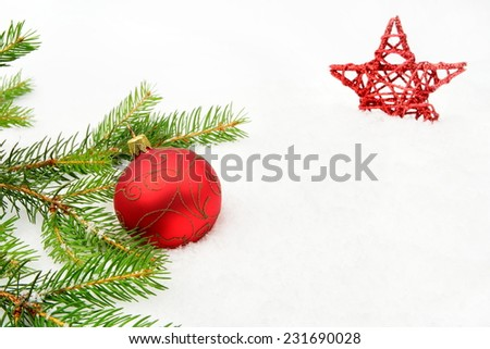 Decoration of red christmas on snow with red star, christmas tree branch on white - stock photo
