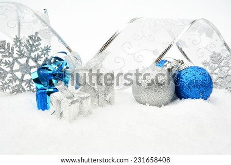 Decoration of silver,blue christmas baubles and gifts with ribbon on snow on white background - stock photo