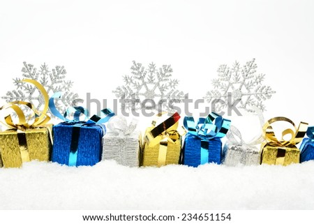 Decoration of silver,blue,golden christmas gifts on snow on white background - stock photo