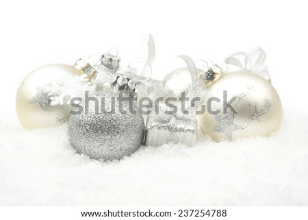 Decoration of silver christmas baubles and gifts in line on snow white background - stock photo