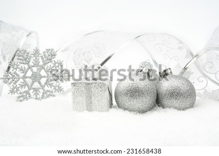 Decoration of silver christmas baubles and gifts with ribbon on snow on white background - stock photo