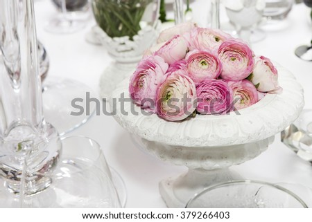 decoration of wedding table. pink ranunculus (persian buttercup) in vase on white table