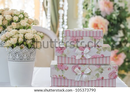 decoration of wedding table. Roses in vase with gift boxes that stand on each other - stock photo