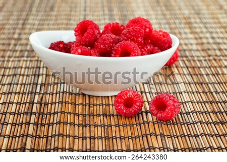 Decoration with raspberries on a bamboo mat - stock photo