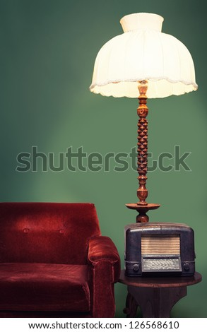 decoration with vintage sofa,shade lamp and a radio on green background - stock photo